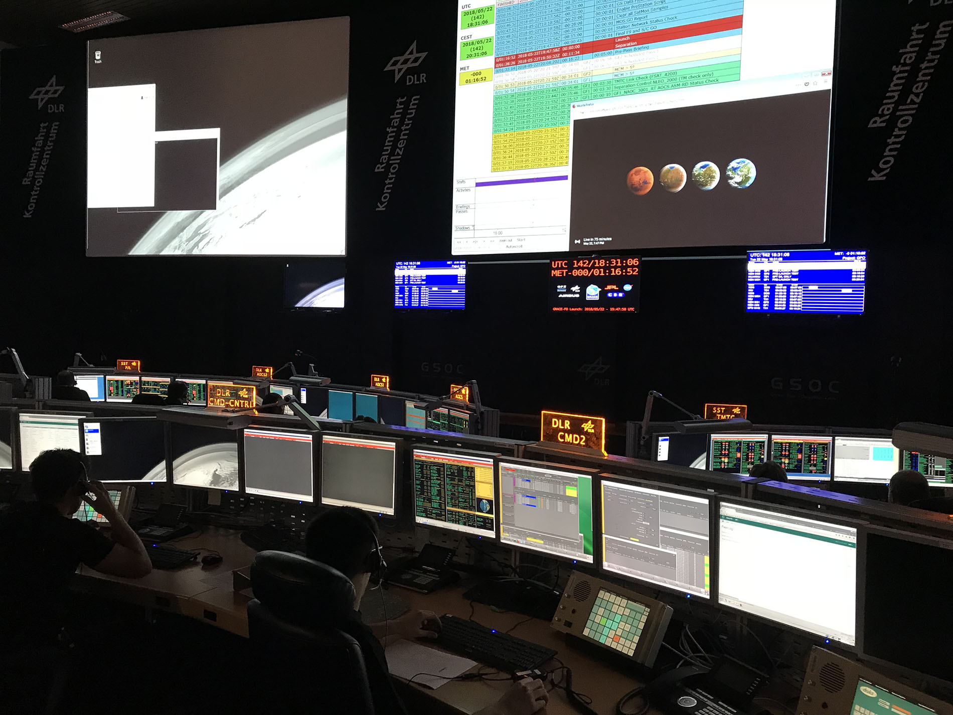 The darkened room of mission control is lighted by computer screens.