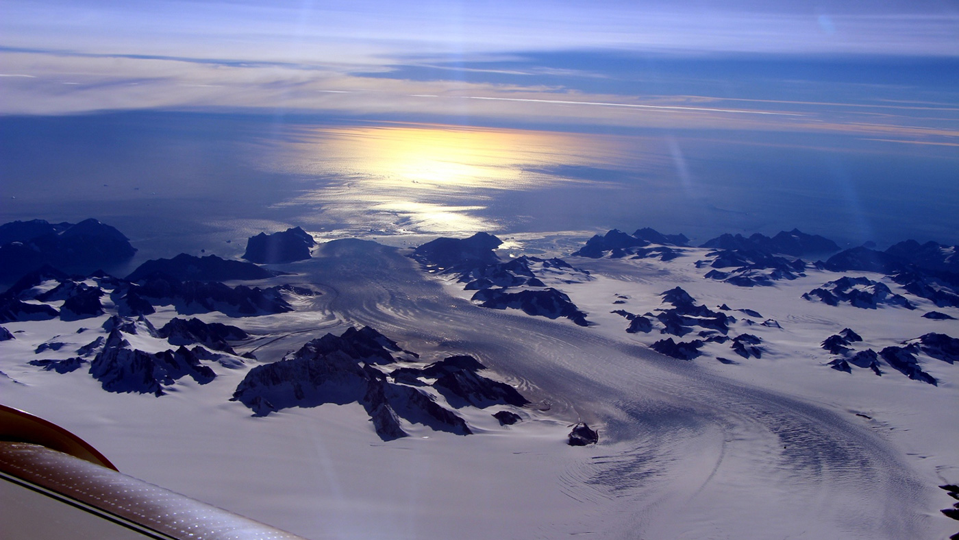 slide 5 - Photo of a glacier from an airplane, with the sun glinting off the ice