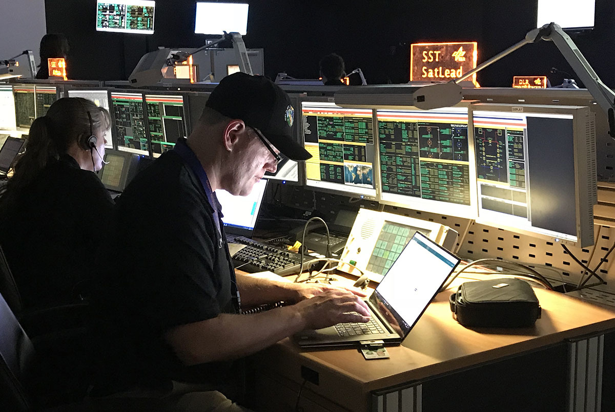 Deputy Project Manager Mike Gross sits at a computer console with multiple screens showing spacecraft status.