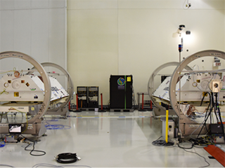 The GRACE-FO satellites, attached to turntable fixtures, at the Astrotech Space Operations processing facility at Vandenberg Air Force Base, California (view 2).