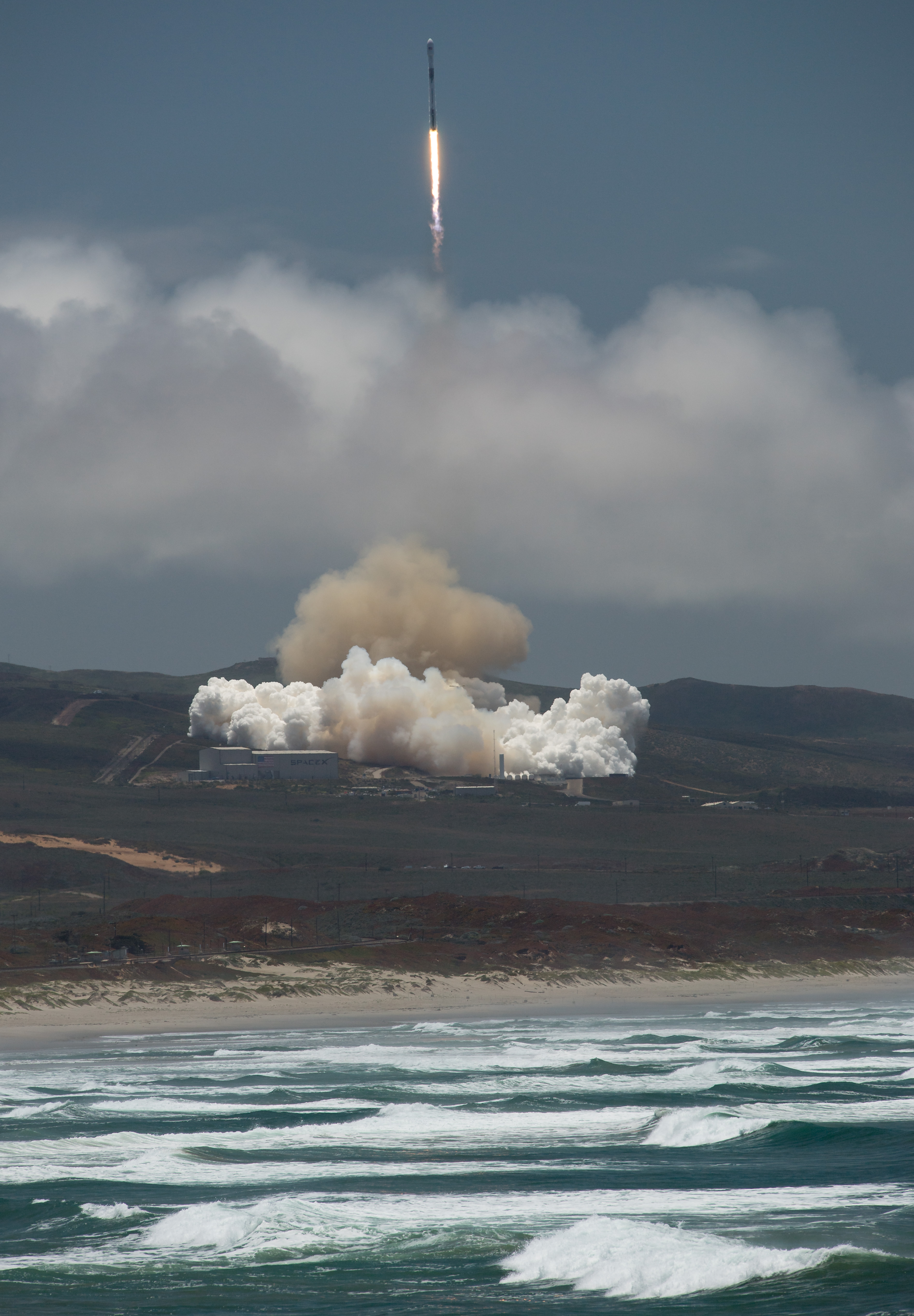 The rocket carrying GRACE-FO blasts off from the launch pad, with the ocean in the foreground.