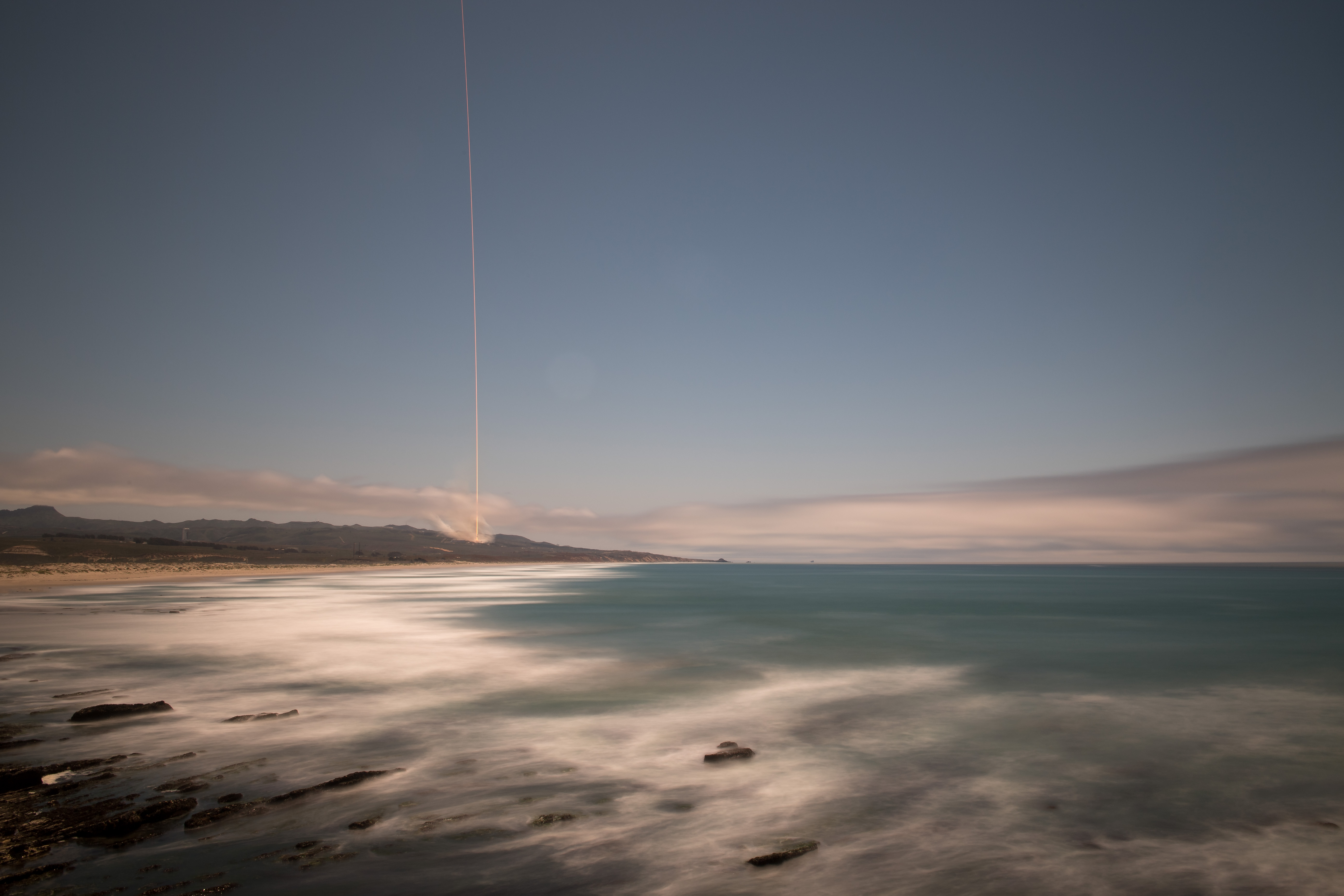 The rocket's blaze is seen across the sky in this long exposure view with the ocean in the foreground.